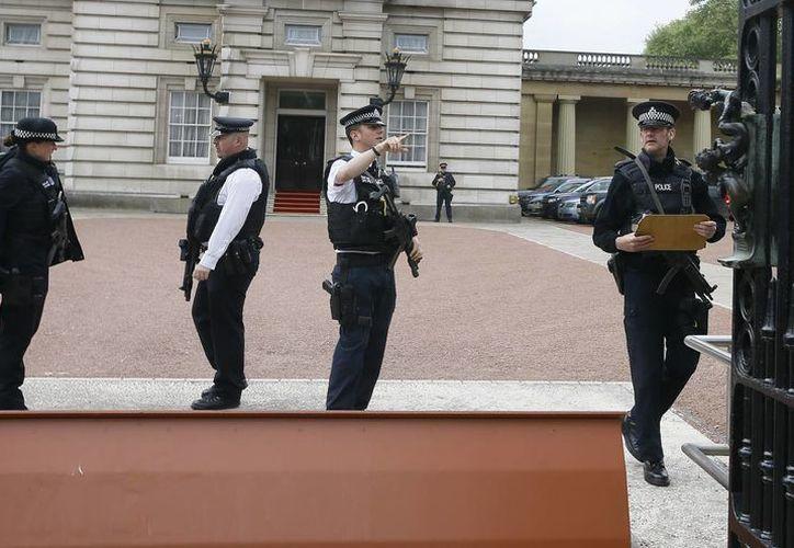 Agentes de policía armados trabajan en la puerta principal del Palacio de Buckingham en Londres, tras la detención de un hombre que intentó entrar al lugar. (Agencias)