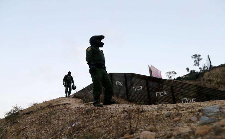 Foto de contexto del 22 de junio de 2016, en el que se ve a agentes de la Patrulla Fronteriza vigilan un tramo de la valla que divide a Tijuana , México, con San Diego, California. (Foto de archivo AP/Gregory Bull)