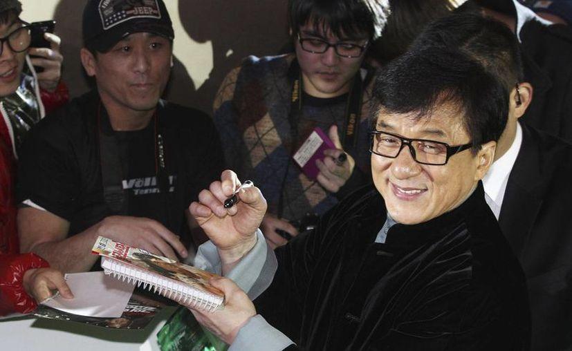 Jackie Chan, en la imagen en una firma de autógrafos en Corea del Sur, está pasando momentos vergonzosos por el caso de su hijo relacionado con drogas. (AP)