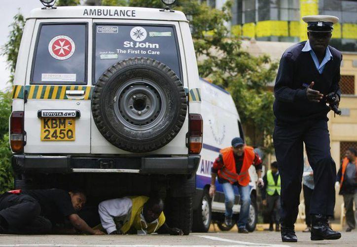 Policías y peatones corren en busca de refugio en los alrededores del Centro Comercial Westgate en Nairobi. (EFE)