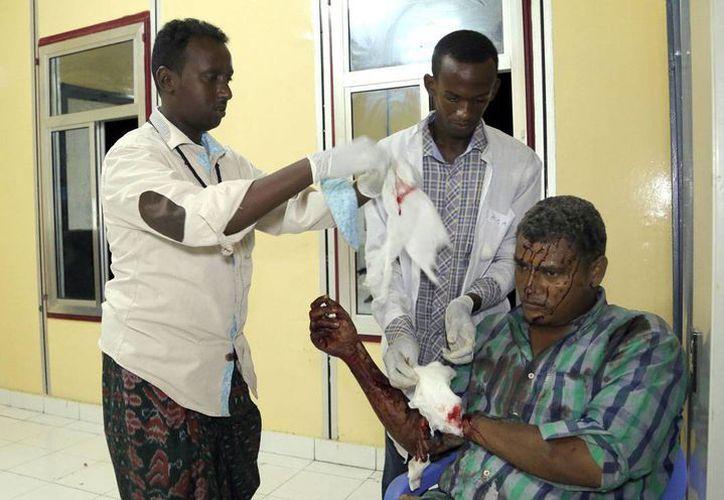 Personal de salud atiende a uno de los heridos durante el ataque a un hotel de Mogadiscio, en Somalia. (AP)