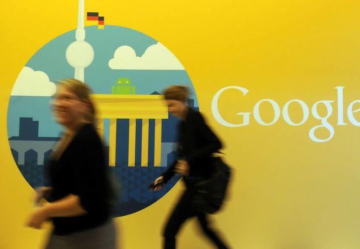 Dos mujeres caminan frente al logo de Google, en las oficinas de la empresa filial de Google en Berlín, Alemania. (Archivo/EFE)