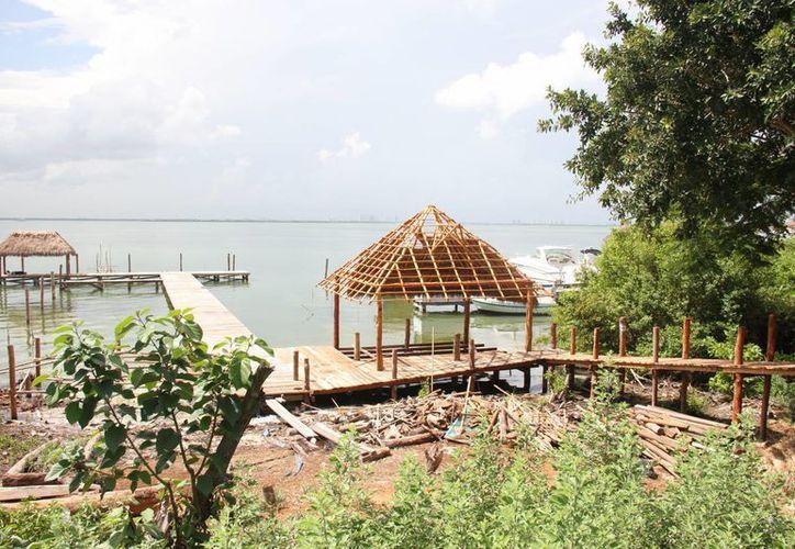 El muelle de madera se construye en la laguna Nichupté. (Consuelo Javier/SIPSE)