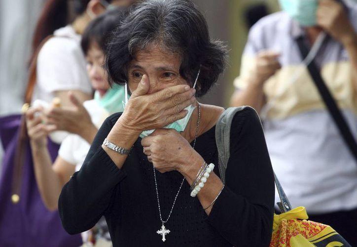 Un familiar de una víctima de vuelo 8501 de AirAsia llora mientras espera la entrega del cuerpo de su pariente en un hospital de la policía en Surabaya, Java Oriental, Indonesia. (Agencias)