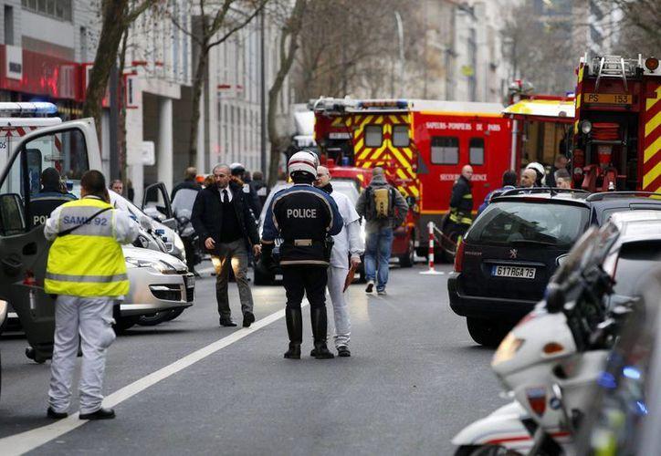 Policías y miembros de los servicios de emergencia congregados en el lugar tras el tiroteo registrado en Mntrouge, al sur de París, Francia hoy. (EFE)