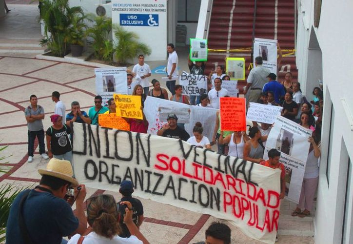 Los manifestantes llegaron a los bajos del palacio municipal en donde se instalaron las mantas. (Daniel Pacheco/SIPSE)