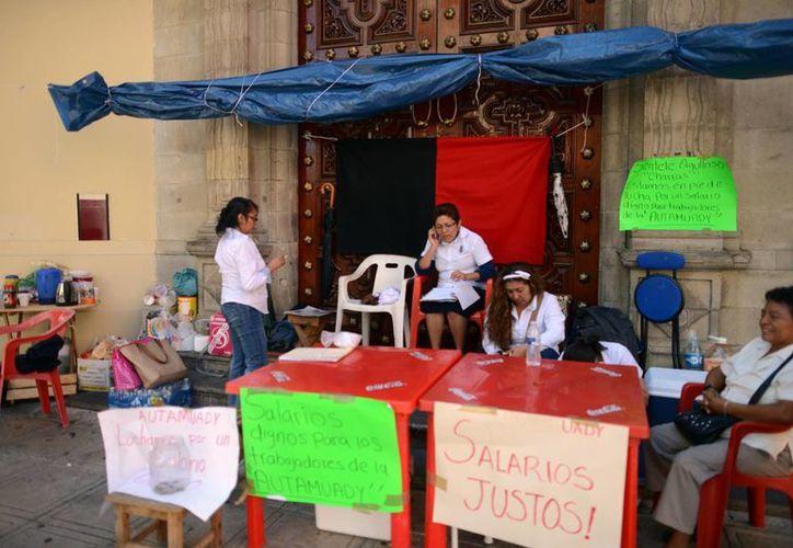 Los trabajadores se mantienen en vigilancia frente la sede de la Uady. (Luis Pérez/SIPSE)