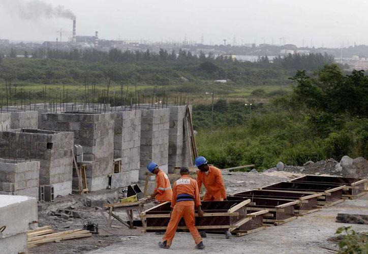 Trabajadores construyen almacenes en un nuevo puerto en construcción en Mariel, Cuba. (Agencias)