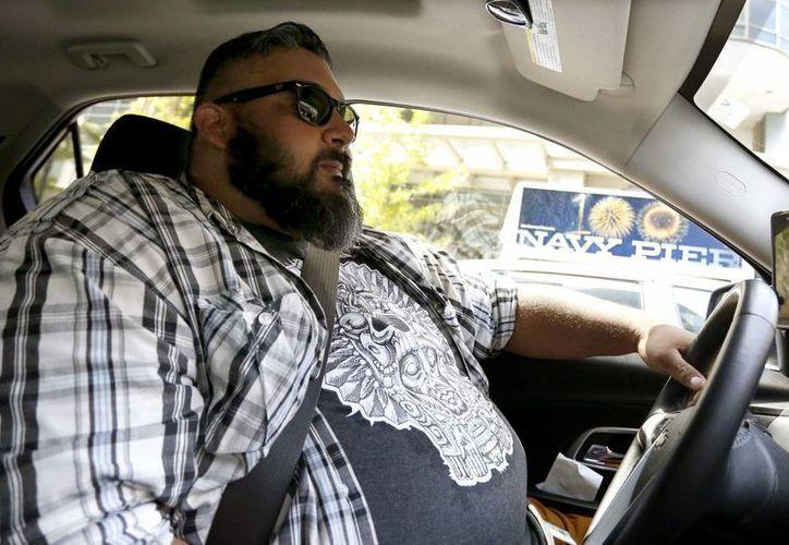 En la imagen, Carlos Correa maneja en Chicago por medio del programa de alquileres Exprfess Drive, de Lyft, una colaboración con GM que permite un alquiler semanal por un vehículo para su uso en el servicio de taxis por appp. (AP Foto/Tae-Gyun Kim)