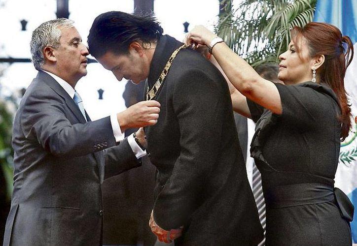 El cantante Ricardo Arjona se manifestó en contra del presidente de su país, Guatemala, Otto Pérez, a quien solicitó su renuncia. En la imagen, el cantante recibe de manos del mandatario la Orden del Quetzal, galardón que devolverá al Gobierno. (prensalibre.com)