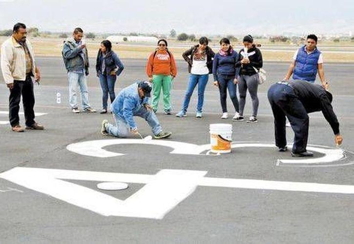 Los maestros de la CNTE tomaron por 11 horas el Aeropuerto de Oaxaca, donde realizaron pintas en las pistas de aterrizaje. (Milenio)