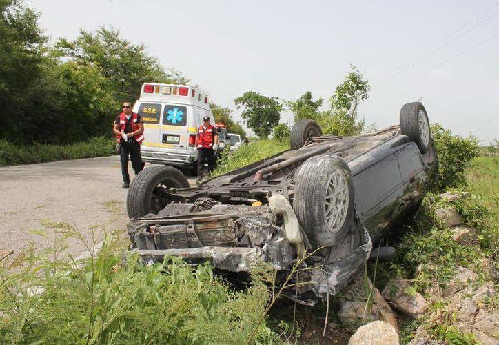 Con las llantas hacia arriba quedó el automóvil, luego de volcar en  la carretera Dzidzantún-Cansahcab. (Milenio Novedades)