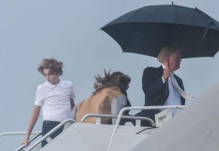 Trump subió al avión oficial, Air Force One, sosteniendo un amplio paraguas, aparentemente dejando que la lluvia mojase a su familia. (Contexto/Internet)