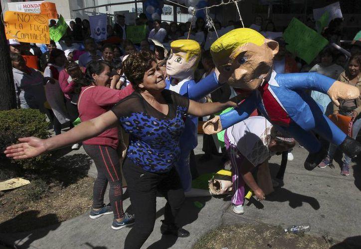 El descontento de los mexicanos contra Donald Trump puede verse reflejado en las tradicionales piñatas, que ya se ofrecen con el rostro del magnate 'para golpearlo' a placer. (AP/Marco Ugarte)