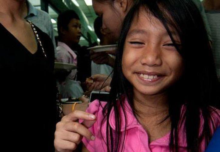 Una niña muestra un platillo durante un concurso de cocina de insectos en Laos, Tailandia. (Agencias)