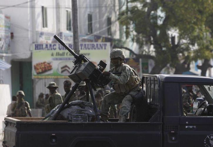 Un soldado somalí toma posición durante los enfrentamientos con los militantes que se encontraban en el interior del Maka Almukaramaha hotel en Mogadiscio. (Agencias)