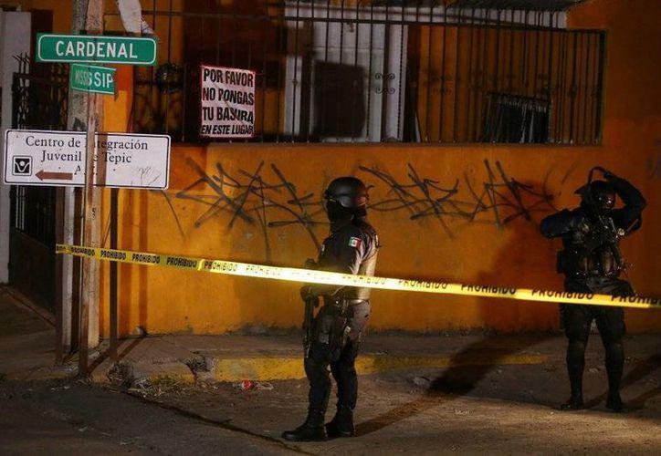 Policías frente a la vivienda del narco Francisco Patrón, 'H2', quien murió durante un enfrentamiento contra fuerzas de la Marina. (Foto: Semar)