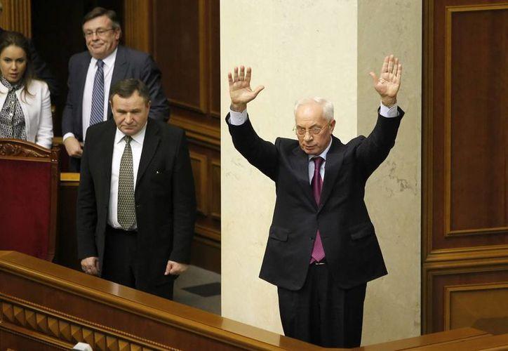 El primer ministro ucraniano, Nikolái Azárov, abandona una sesión parlamentaria en Kiev, después de que el Parlamento rechazase la moción de censura al gobierno. (EFE)
