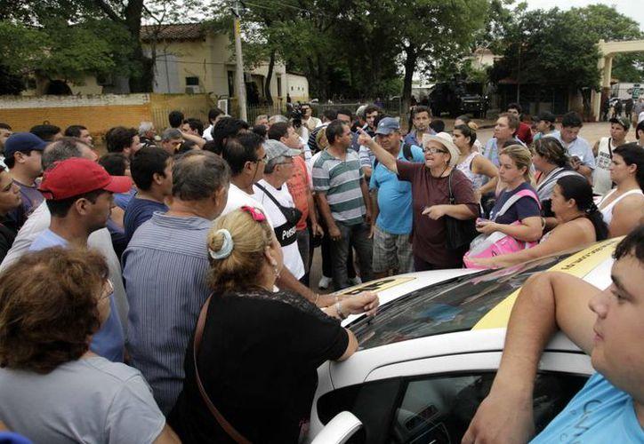 """Un grupo de """"paseros"""" se manifiesta, este martes 3 de diciembre de 2013, en la zona del puerto Itá Enramada, Paraguay, en frontera con la argentina Clorinda. (EFE)"""
