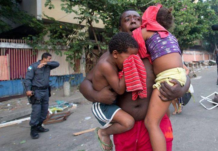 Unas 5,000  familias que habían tomado el edificio, exsede de una empresa de televisión, fueron desalojadas violentamente por la Policía. Molestos, los vecinos arremetieron contra las fuerzas del orden. (AP)