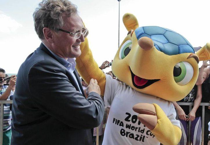 El secretario general de la FIFA, Jérôme Valcke (i), posa con la mascota del Mundial de Fútbol Brasil 2014, Fuleco, durante una visita a la playa de Iracema, donde se celebrará una de las 'Fan fest'. (EFE)