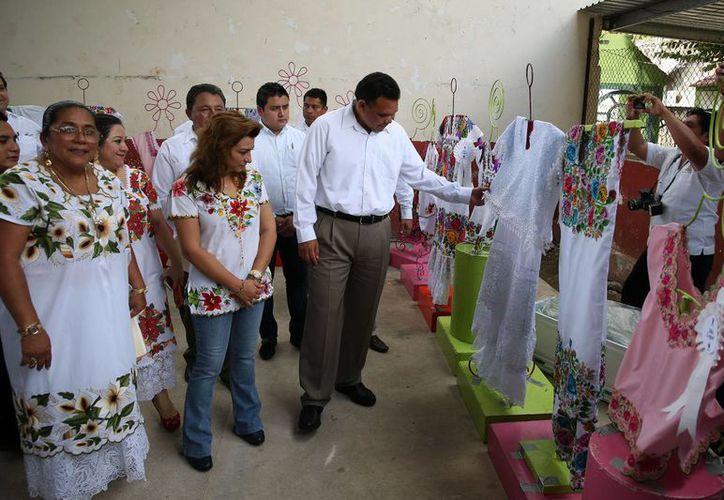 El gobernador Rolando Zapata Bello y su esposa Sarita Blancarte admiran la calidad de los bordados que participaron en el concurso 'Puntadas con magia'. (SIPSE)