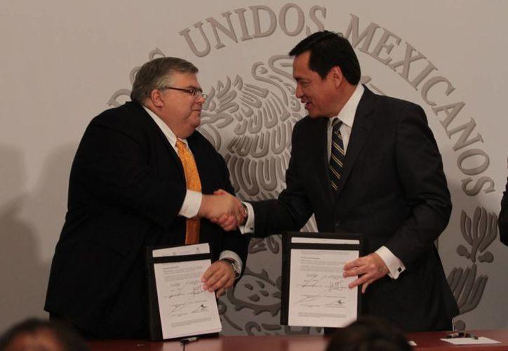 Agustín Carstens (i) con el titular de la Segob, Miguel Osorio Chong, durante una firma de acuerdos entre  Banxico y la dependencia. (Notimex)