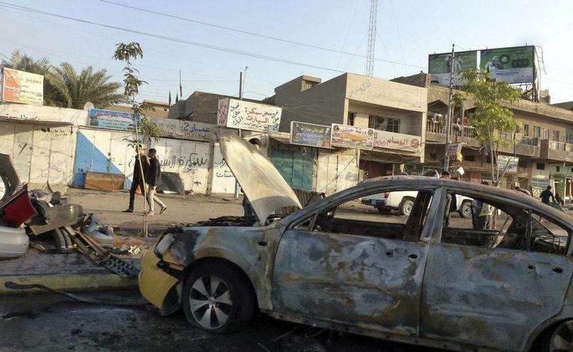 Peatones iraquíes caminan por la zona de un atentado terrorista en Bagdad, perpetrado el 3 de diciembre.  (EFE/Foto de archivo)