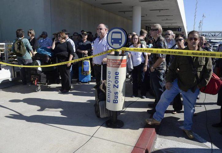 Pasajeros esperan detrás de una línea de seguridad de policía, mientras cientos son evacuados tras el tiroteo. (EFE)