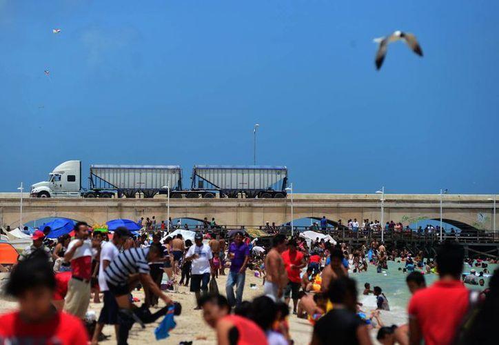 Poco más de 40 mil paseantes abarrotaron la playa del malecón, bajo un clima muy caluroso. (Luis Pérez/SIPSE)