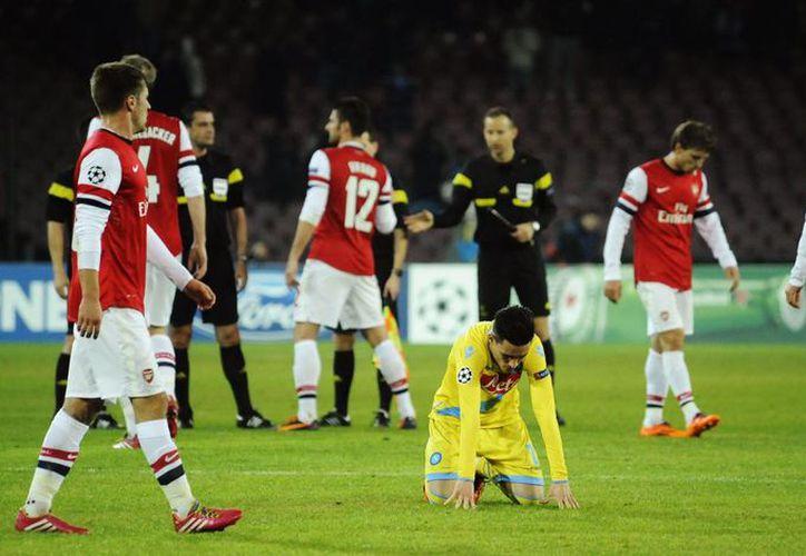 El goleador del Nápoles, José Callejón, yace en el pasto rodeado por rivales del Arsenal. El equipo ítalo venció al inglés, pero éste último fue el que avanzó a octavos de final en la <i>Champions</i>. (Agencias)