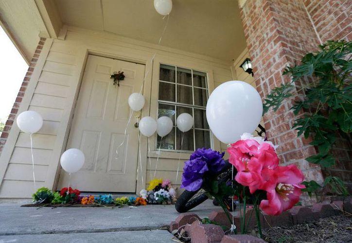Vecinos y familiares colocaron globos y flores a las puertas de la vivienda en donde un hombre mató a toda la familia de su exesposa. (AP)