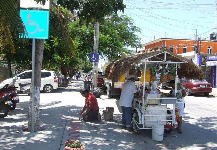 Comerciantes de la colonia Centro, ponen su basura en la calle, obstruyendo pasos especiales para personas discapacitadas. (Rossy López/SIPSE)