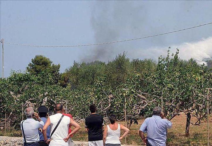 En la imagen, un grupo de personas observa las maniobras aéreas para controlar el fuego en Modugno. El saldo fue de siete muertos y una decena de heridos. (Foto EFE)