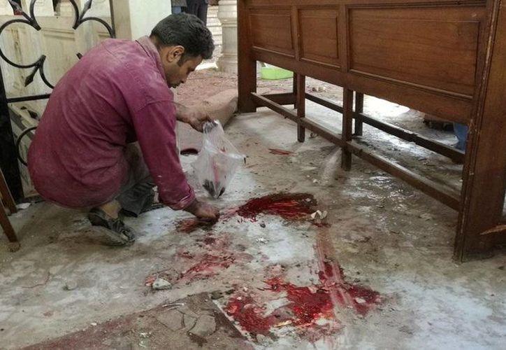 Un trabajador limpia dentro de la catedral de San Marcos en el centro de El Cairo tras un atentado, este domingo 11 de diciembre de 2016. (Omar El-Hady via AP)