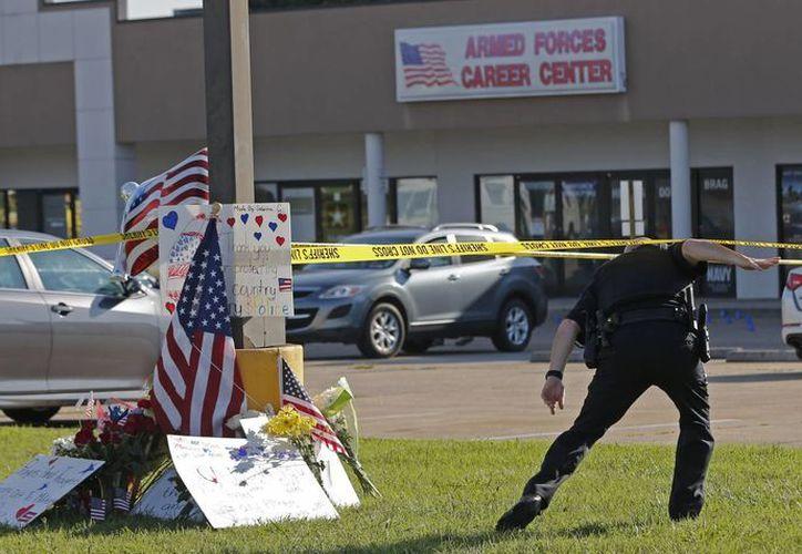 Un agente de policía pasa bajo la cinta frente a un centro de reclutamiento de las fuerzas armadas en Chattanooga, Tennessee, donde un hombre abrió fuego y mató a varios efectivos. El atacante también murrió. (AP Foto/John Bazemore)