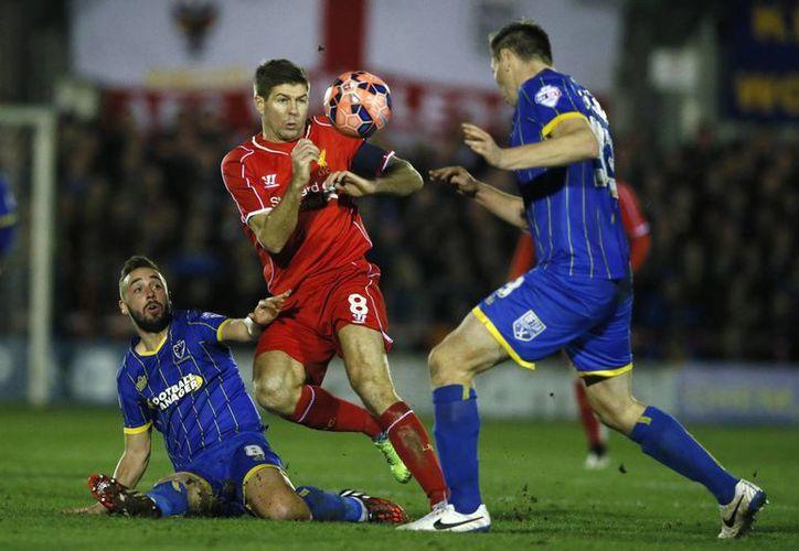 El capitán y emblema del Liverpool, Steven Gerrard (de rojo), trata de avanzar entre Sammy Moore yJon Goodman, del Wimbledon en partido de la FA Cup. (Foto: AP)
