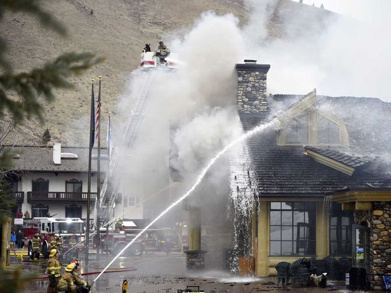 Firefighters work to extinguish a blaze that heavily damaged the Warm Springs Lodge. (AP)