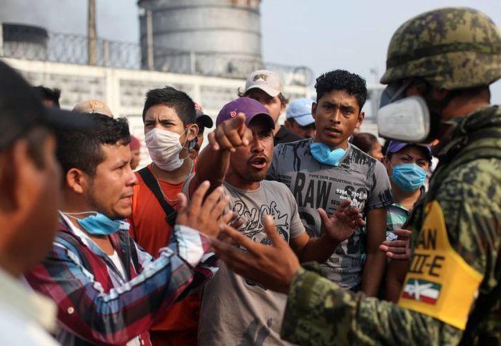 Un familiar de un trabajador del complejo petroquímico Pajaritos discute con un soldado del ejército mexicano, al cual le pide información sobre el incidente que cobró la vida de 28 personas. (Agencias)