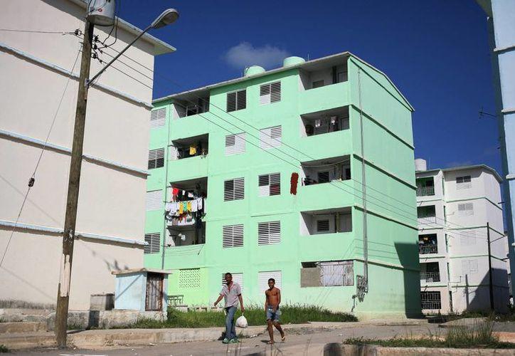 Dos hombres caminan en una nueva urbanización ubicada en La Habana, Cuba, construida como parte de un programa de nuevas viviendas que se inició en marzo y abril de 2013. (EFE)