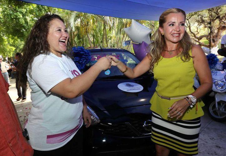 Ruby Rossina Villanueva Trejo recibe de la tesorera municipal, Claudia Canto Mézquita, la llaves del auto que ganó en el sorteo del predial. (SIPSE)