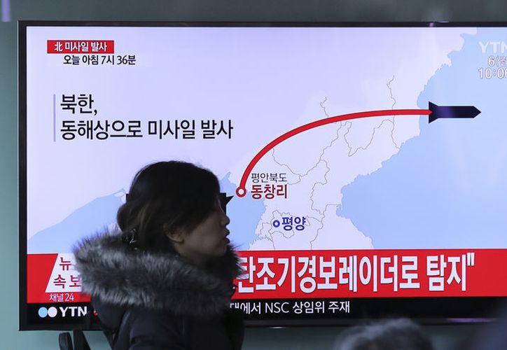Una persona camina frente a una pantalla de televisión que muestra un noticiero reportando el lanzamiento de un misil de Corea del Norte. (AP/Lee Jin-man)
