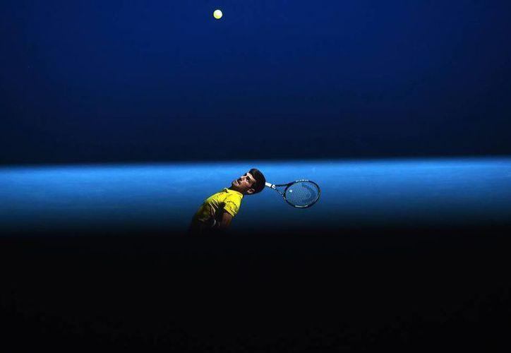 La 'oscuridad' cubre ahora al deporte blanco por el supuesto amaño de partidos. El propio número 1 del mundo, Novak Djokovic (en la imagen, durante su primer partido en el Abierto de Australia), reconoció que le ofrecieron 200 mil dólares por 'dejarse ganar'. (EFE)