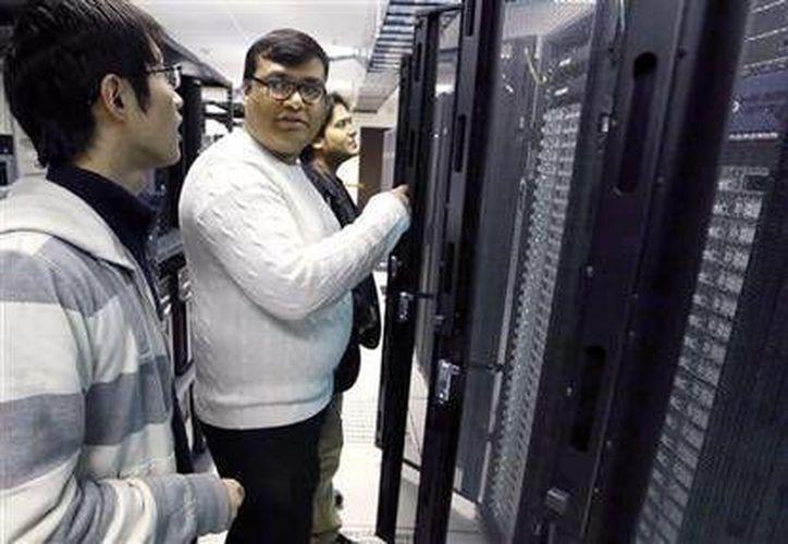 Abhinav Gupta (c) habla con Xinlei Chen (izq.) mientras Abhinav Shrivastava (al fondo) observa uno de los clusters de computadores utilizados en la Universidad Carnegie Mellon, en Pittsburgh, el jueves 21 de noviembre de 2013. (Foto AP/Keith Srakocic)