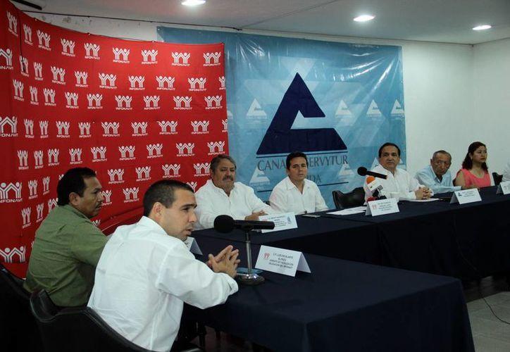 El presidente de la Canaco Mérida, José Manuel López Campos, y el delegado del Infonavit, Miguel Enríquez López, anunciaron la cuarta jornada de mediación. (SIPSE)