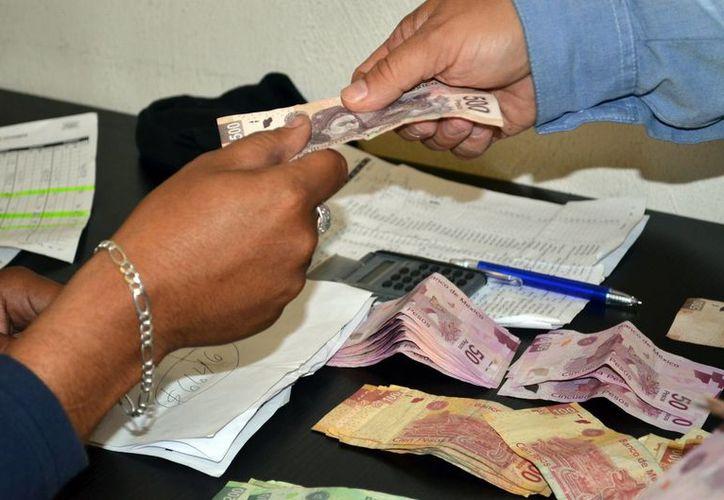 Concluye periodo para pagar el aguinaldo para los trabajadores. Imagen de un empleado al momento de recibir su prestación laboral. (Archivo/SIPSE)