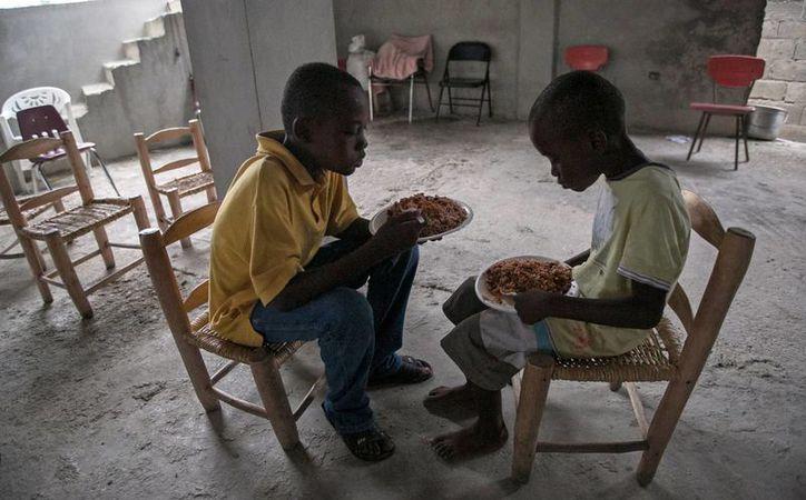 Niños haitianos descansan, comen y juegan en la iglesia de Croix des Bouquets, al este de la ciudad de Puerto Príncipe, Haití, donde se refugian del huracán 'Matthew'. (Notimex)