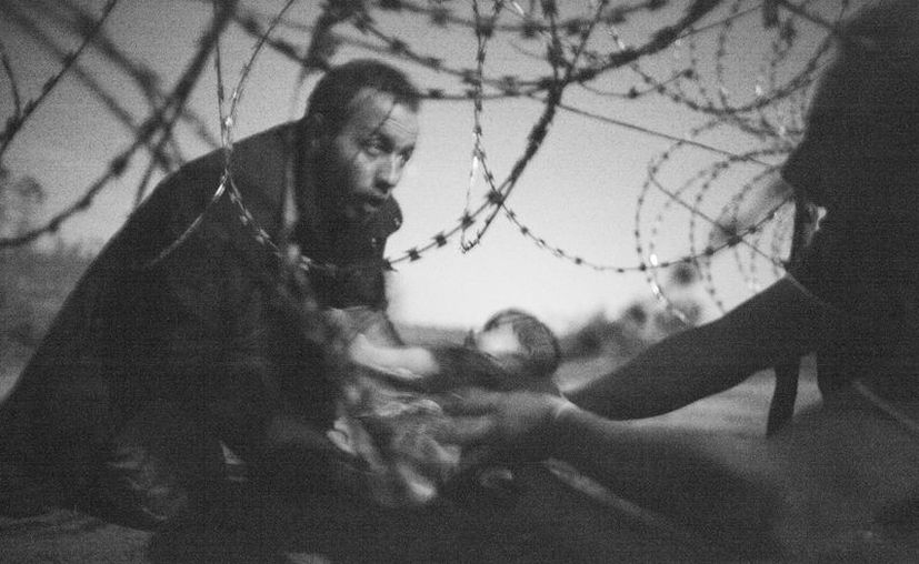 """Imagen de de la Mejor Fotografía del Año de WPP. """"Esperanza de una nueva vida"""". Unos hombres y un bebé bajo los alambres de la frontera entre Serbia y Hungría, por Warren Richardson. (WPP)"""