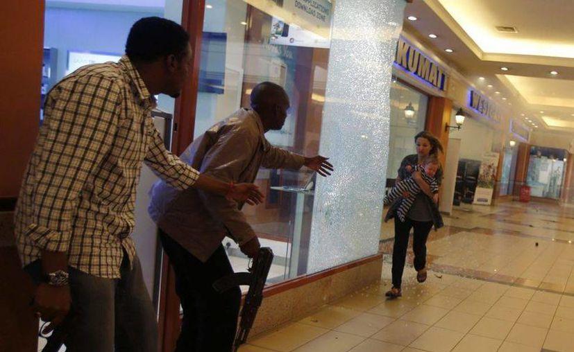 La policía ayuda a una mujer y su hijo a protegerse de los disparos. (Reuters)
