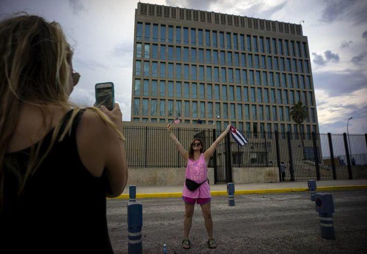 Una ciudadana estadounidense toma una foto a su compañera mientras sostiene una bandera de Cuba y de EU frente a la embajada estadounidense en La Habana, Cuba. (Agencias)